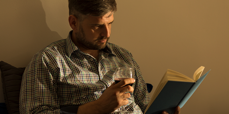 Man drinking wine while reading a book